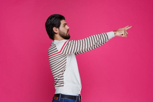 Mann zeigt auf etwas oder präsentiert jemanden.
