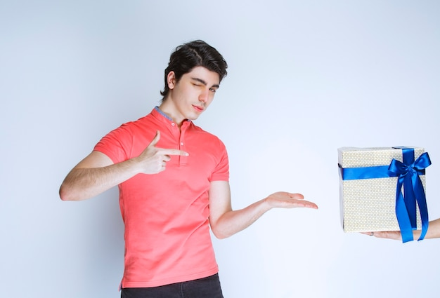 Mann zeigt auf seine weiße geschenkbox mit blauem band