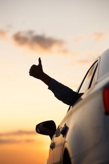 Mann zeigt daumen hoch / macht like / ok zeichen mit der hand vom autofenster mit sonnenuntergang himmel, entspannend, genießt roadtrip und fühlt die luft und freiheit