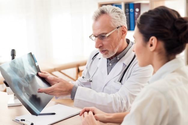 Mann zeigt der frau röntgenstrahl. die leute sitzen am schreibtisch.