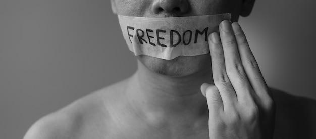 Mann zeigt drei finger mit in klebeband versiegeltem mund mit freiheitsbotschaft. meinungsfreiheit, menschenrechte, protestdiktatur, demokratie, freiheit, gleichheit und brüderlichkeitskonzepte
