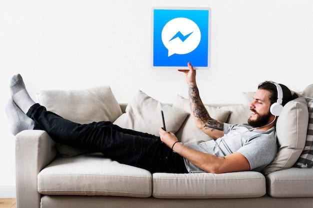 Mann zeigt ein facebook messenger-symbol