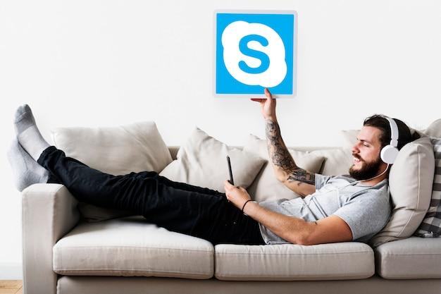 Mann zeigt ein skype-symbol