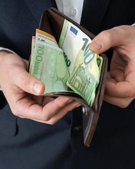 Mann zeigt eine brieftasche mit geld im inneren