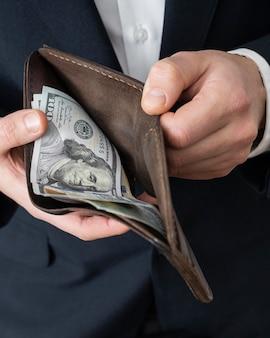 Mann zeigt eine brieftasche mit geld