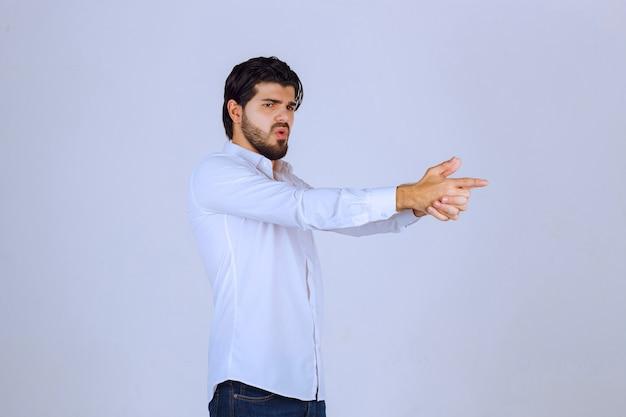 Mann zeigt handfeuerwaffenzeichen.