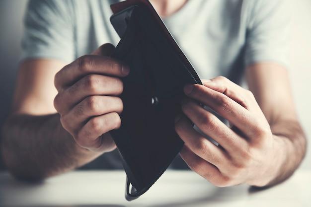 Mann zeigt leere brieftasche