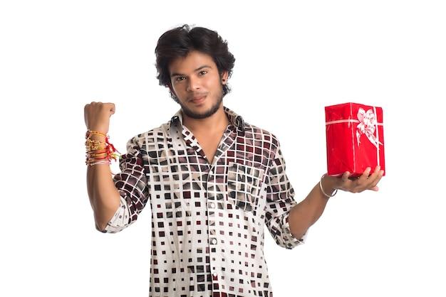 Mann zeigt rakhi auf seiner hand mit einkaufstüten und geschenkbox anlässlich des raksha bandhan festivals.