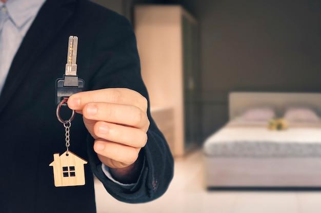 Mann zeigt schlüssel mit schlüsselbund in form eines kleinen hauses in eine neue wohnung auf unscharfem hintergrund des schlafzimmers mit modernem interieur