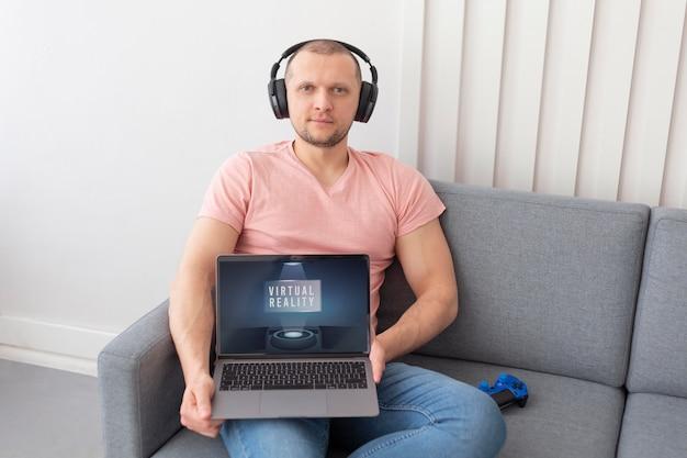 Mann zeigt seinen laptop für videospiele