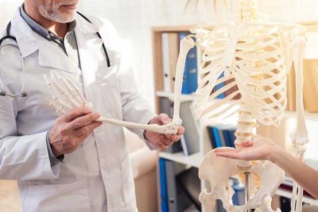 Mann zeigt skeletthand. frau gestikuliert.