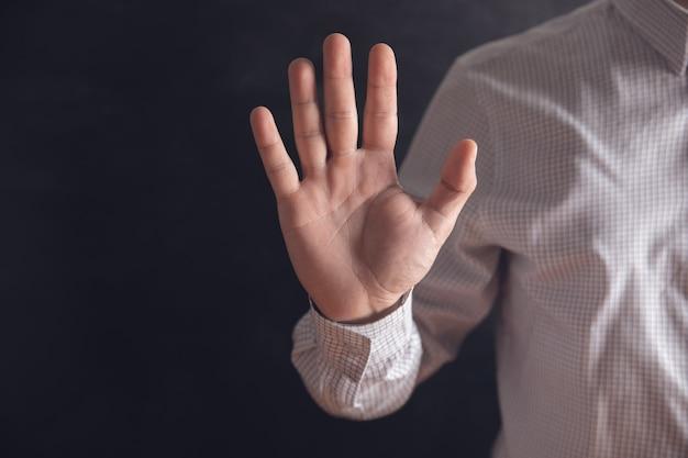 Mann zeigt stopp mit einer hand.