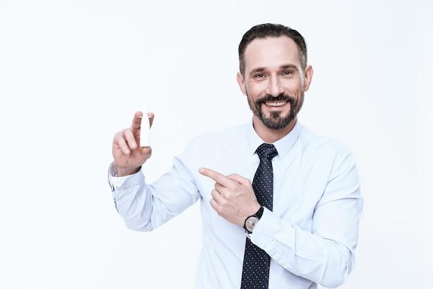 Mann zeigt weiße nasentropfen auf einem weißen hintergrund.