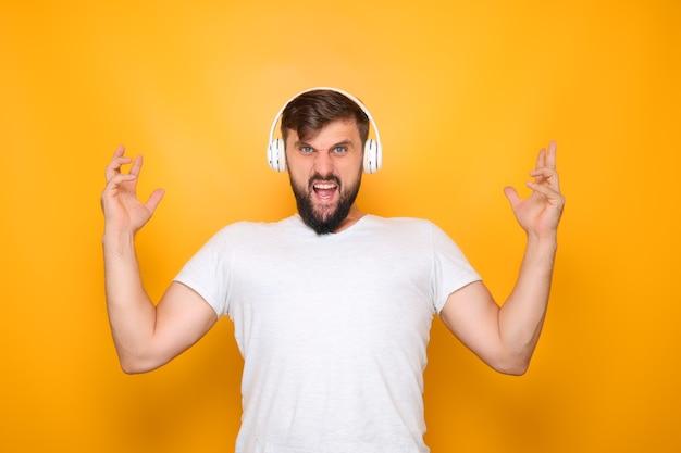 Mann zeigt zähne, die die hände hochheben und hört musik
