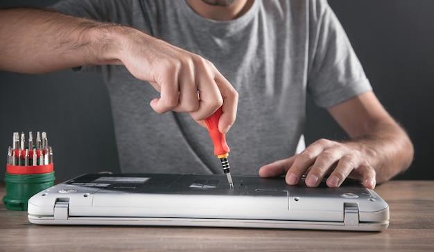 Mann zerlegt einen laptop mit einem schraubendreher.
