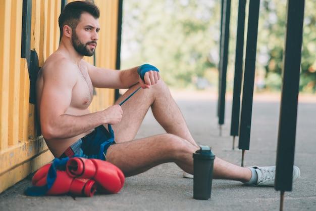 Mann zieht boxbandagen sitzt auf dem asphalt. homosexuell in sportbekleidung bereitet sich auf sparring vor. boxring unter freiem himmel. draußen kämpfen.