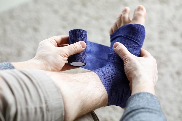 Mann zieht stretch an seinem bein mit elastischem verband