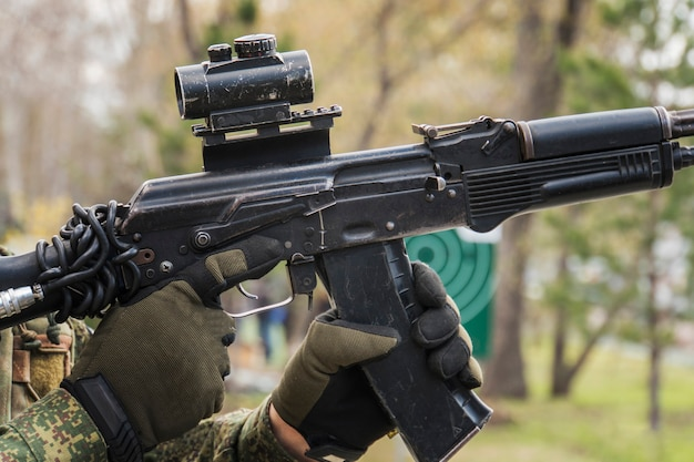 Mann zielt mit einer ak-47 mit reflexvisier, separatist. männermagazine in der kalaschnikow. das gewehr nachladen. clip-ersatz. schießen üben. ausbildung in der armee. ausbildung von soldaten