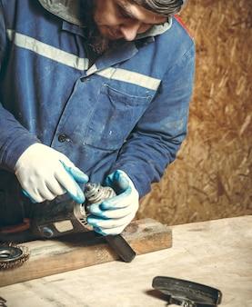 Mann zimmermann bei der reparatur ihrer arbeitsgeräte in seiner werkstatt