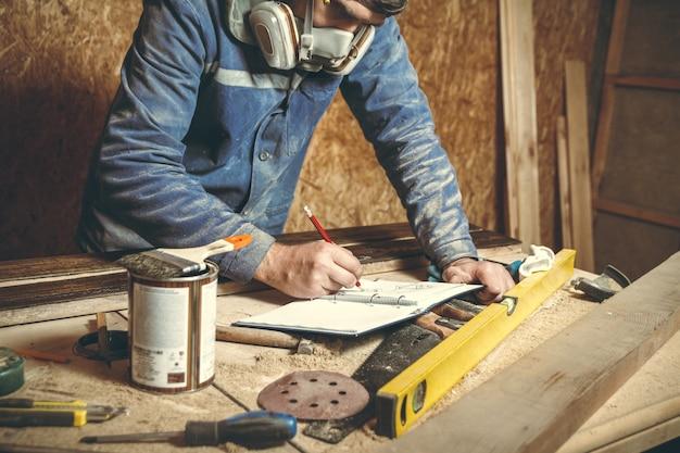Mann zimmermann, der mit holz arbeitet und skizzen in bleistift in einem notizbuch zeichnet