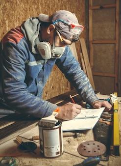 Mann zimmermann in seinem heimstudio arbeitet mit holz und zeichnet skizzen mit bleistift in ein notizbuch