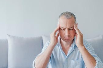 Mann zu Hause, der Kopfschmerzen hat