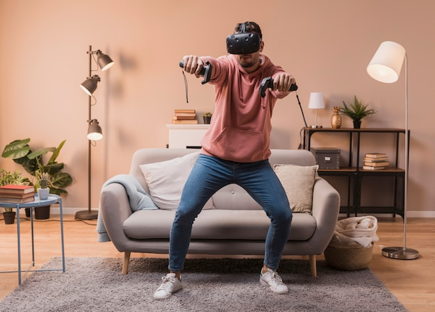 Mann zu hause, der mit virtuellem kopfhörer spielt