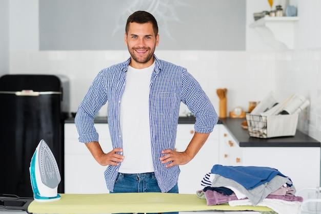 Mann zu hause, der sich vorbereitet, kleidung zu bügeln