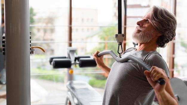 Mannansicht des seitenansichts im fitnessstudio