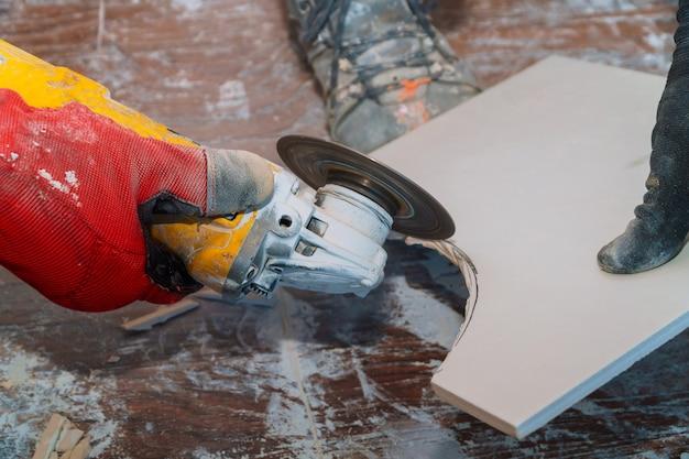 Mannarbeitskraft-ausschnittfliese mit kreissäge im bau