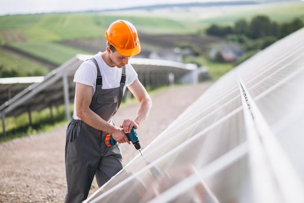 Mannarbeitskraft im firld durch die sonnenkollektoren
