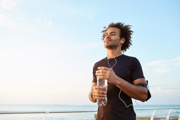 Mannathlet trinkt wasser aus plastikflasche nach hartem laufendem training. dunkelhäutiger männlicher sportler, der den himmel beim laufen betrachtet und die ansicht genießt
