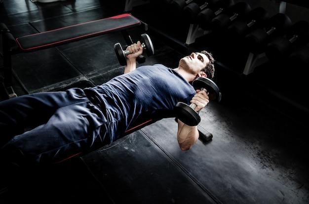 Mannaufnahme dumbell in der turnhalle. übung mit trainingsprogramm für gesundes
