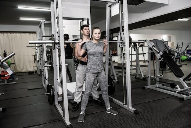 Mannausbilder, der mit frau im fitnessstudio arbeitet