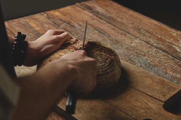 Mannbäcker, der ein messerbrot auf einem hölzernen schneidebrett auf altem hölzernem hintergrund schneidet