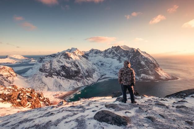 Mannbergsteiger, der auf schneebedecktem berg bei sonnenuntergang steht