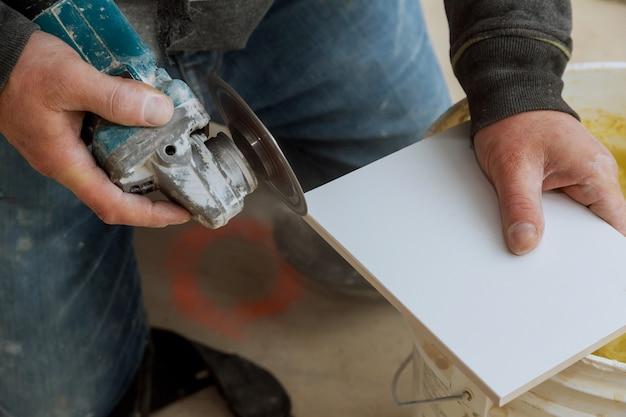 Mannberufsarbeiter-ausschnittfliese mit der kreissäge elektrisch
