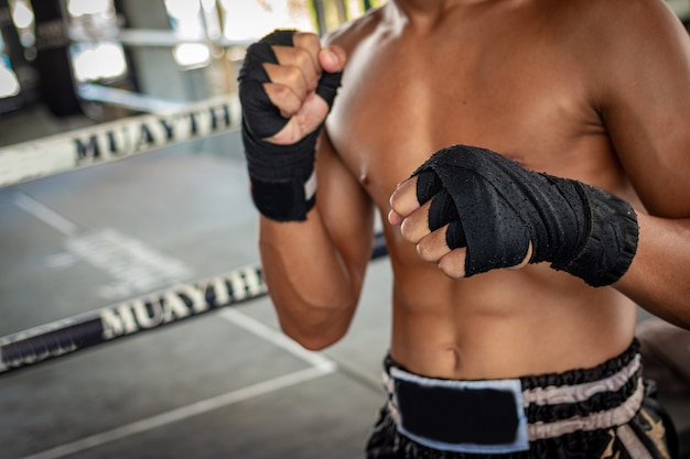 Mannboxer, der seine hand im verpackenarenasport einwickelt.