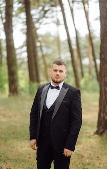 Mannbräutigam in stilvollem anzug posiert