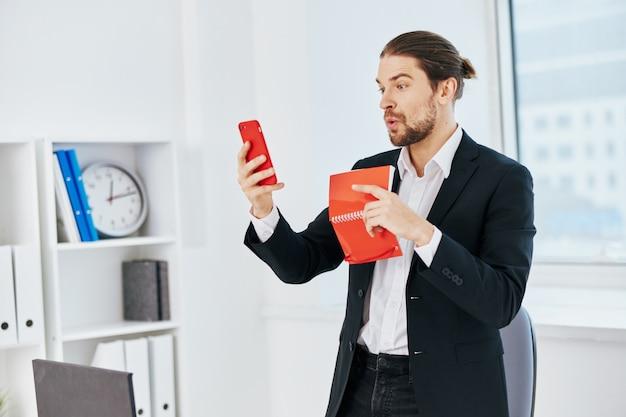 Mannbüroarbeitsdokumente mit einem telefon in der handtechnologie