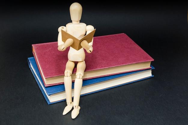 Mannequin, das auf dem lesen mit zwei büchern sitzt