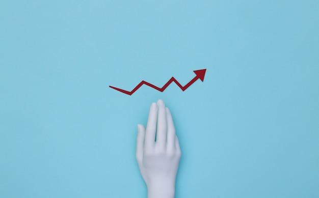 Mannequins hand und roter wachstumspfeil, der auf blauem grund nach oben neigt.