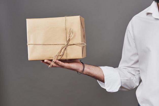 Mannes hände geben paket in braunes papier gewickelt und mit grobem bindfaden gebunden
