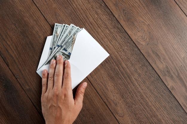 Mannes hand und dollar der usa in einem weißen umschlag