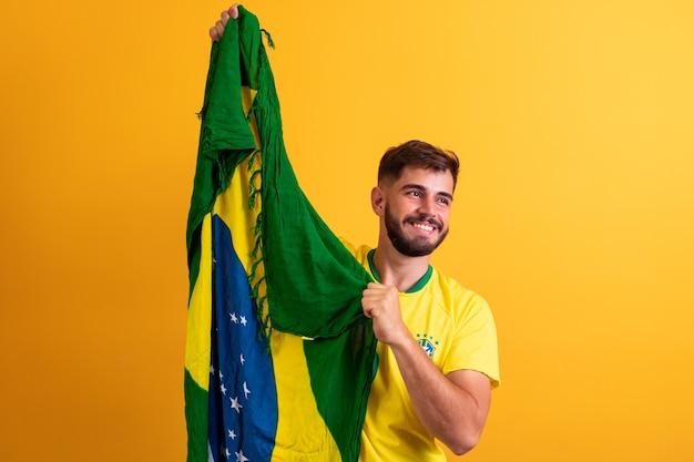 Mannfan, der einen gelben hintergrund der brasilianischen flagge hält. brasilien-farben im hintergrund, grün, blau und gelb. wahlen, fußball oder politik.
