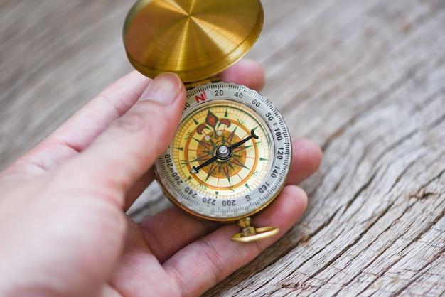 Mannforscher, der richtung mit kompass für karte sucht. navigationskompassreise- und touristenkonzept