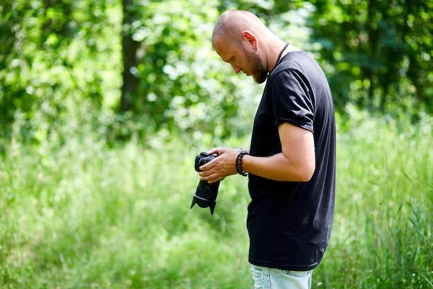 Mannfotograf mit einer fotokamera in der hand im freien