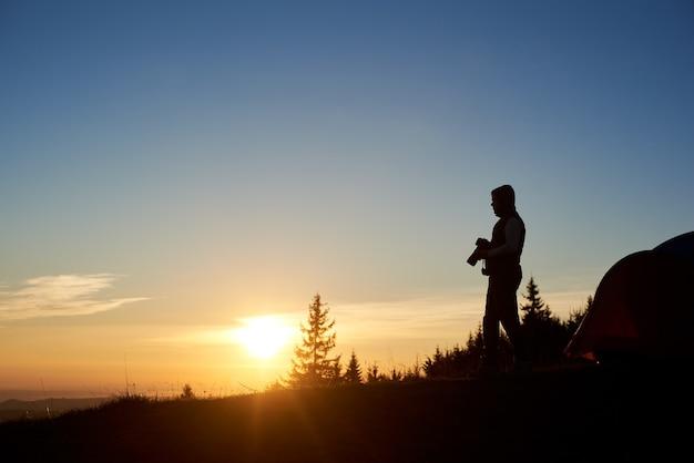 Mannfotograf mit fotokamera in den bergen bei sonnenuntergang