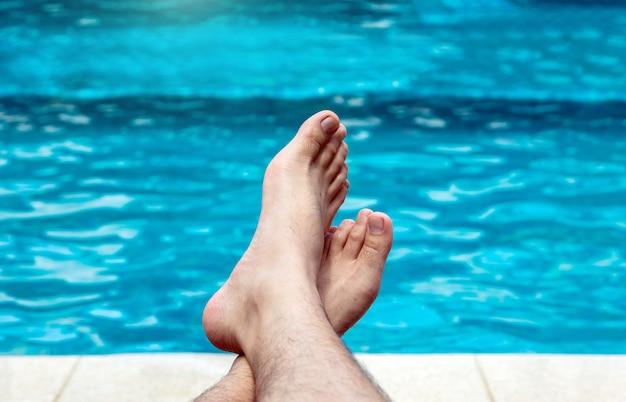 Mannfüße, die nahe schwimmendem hintergrund im sommer sich entspannen