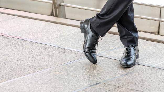 Mannfüße in schwarzen lederschuhen stehen auf betonboden.